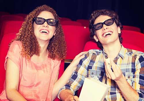 映画を見て笑うカップル