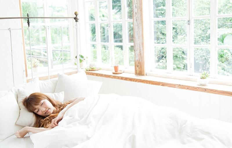 カーテンを開けて眠る女性