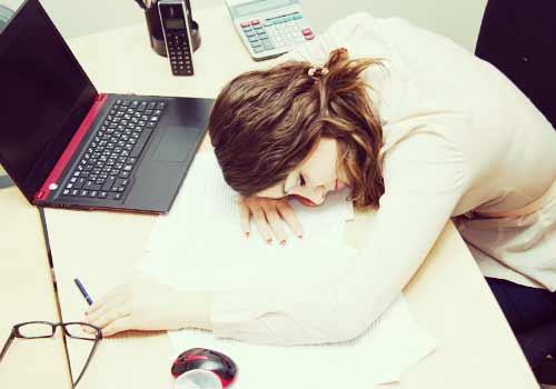 仕事場で居眠りする女性