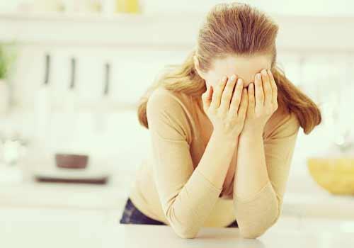 キッチンで落ち込む女性