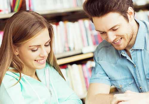 図書館で会話するカップル