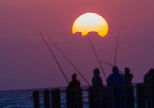 夜明けに釣りをする人たち