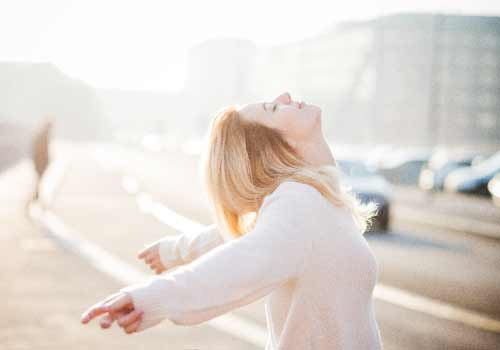 太陽の下で背伸びをする女性