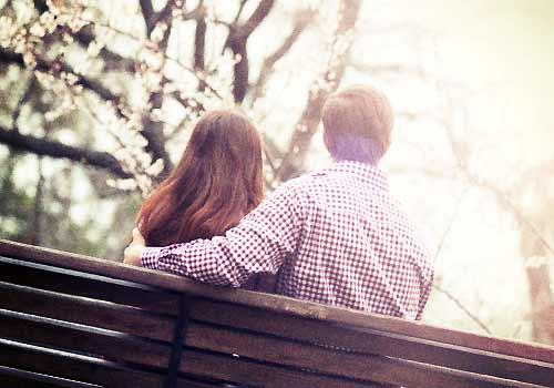 ベンチに座り桜を眺める恋人たち
