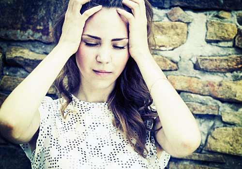 頭を抱え悲しむ女性
