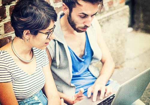 パソコンで勉強を教える男性と教わる女性