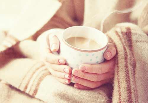 コーヒーで暖まる女性