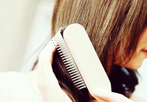 髪の毛をブラッシングする女性