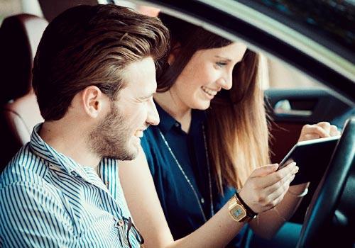 車の中でCDを見るカップル