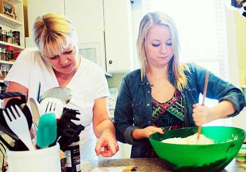 母親から料理の指導を受ける女性