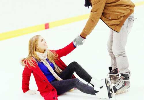 スケートで転んだところを彼氏に助けてもらう女性