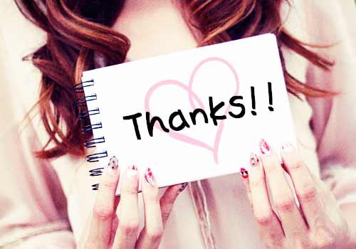 英語で「ありがとう」とメッセージを掲げる女性