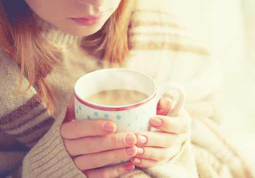 暖かい飲み物を飲む女性