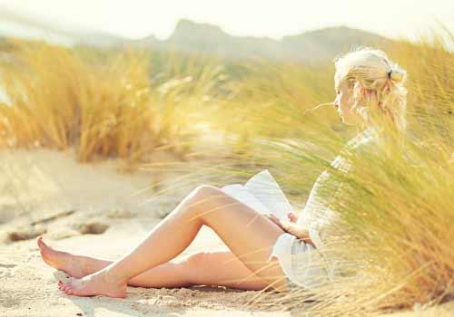 砂浜で本を読む女性