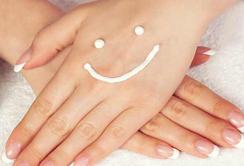 手に笑顔をペイントしたクリーム