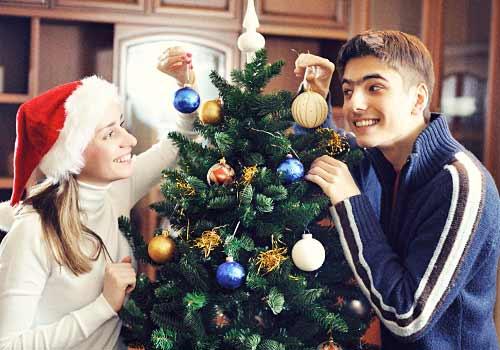 クリスマスツリーの飾りつけをするカップル