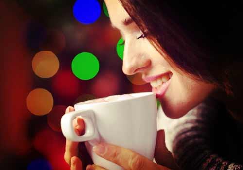 暖かいコーヒーを飲む女