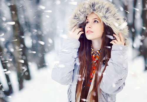雪の降る空を見上げる女性