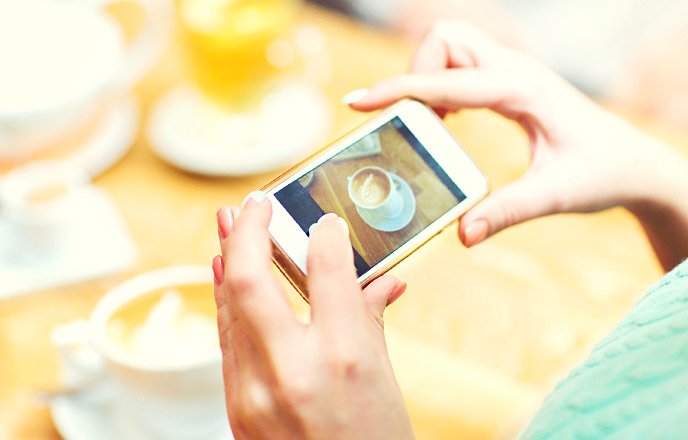 スマホでコーヒーの写真を撮る女性