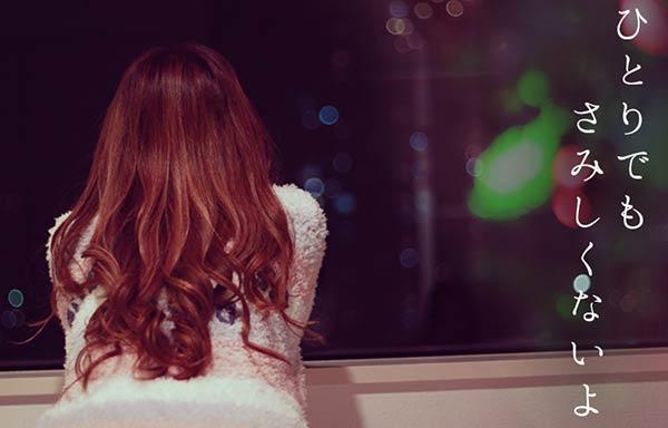 窓から夜の街を眺める女