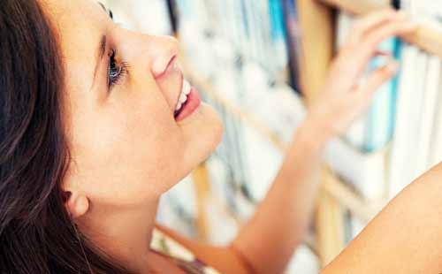 本棚から本を探す女性