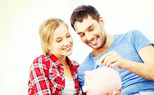 貯金箱にコインを入れるカップル