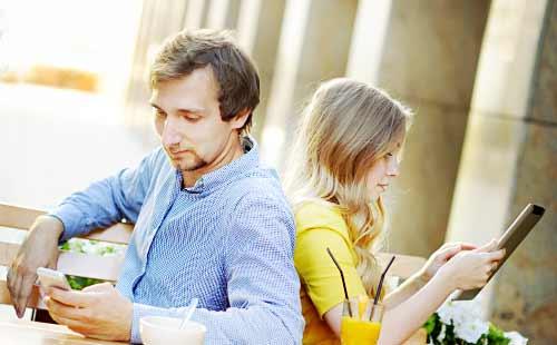 タブレットを見る女とスマホを見る男