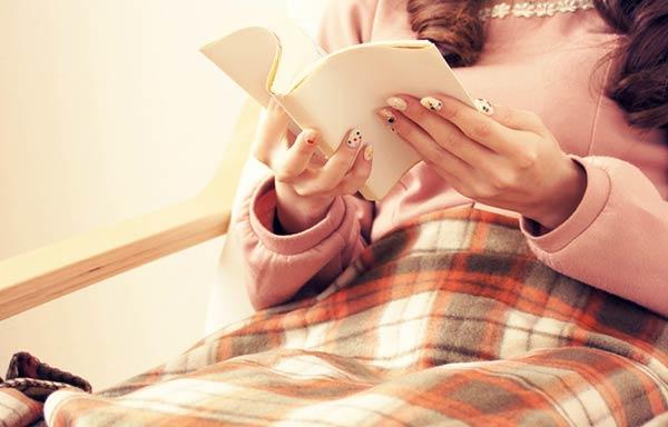 ひざ掛けをして本を読む女性