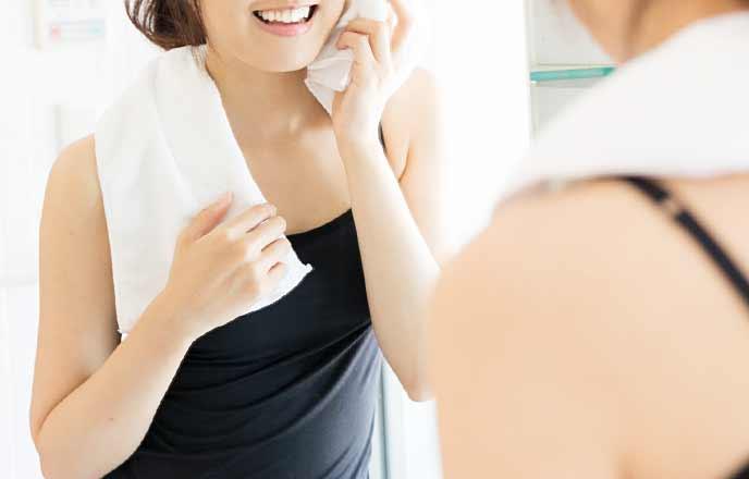 汗をタオルで拭く女性