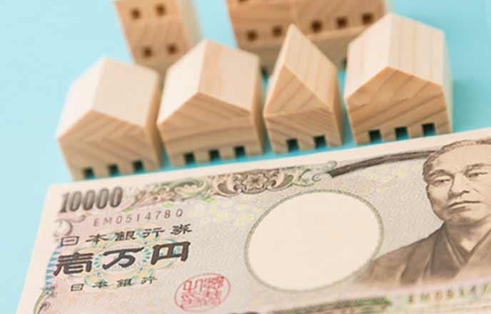木でできたミニチュアの家と一万円札