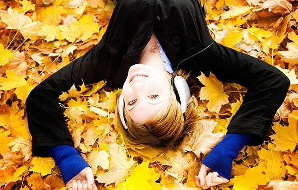落ち葉の上で寝ころんで音楽を聴く女性