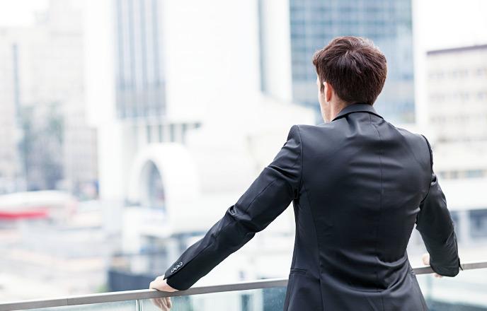 ビルの並ぶ街を眺める男