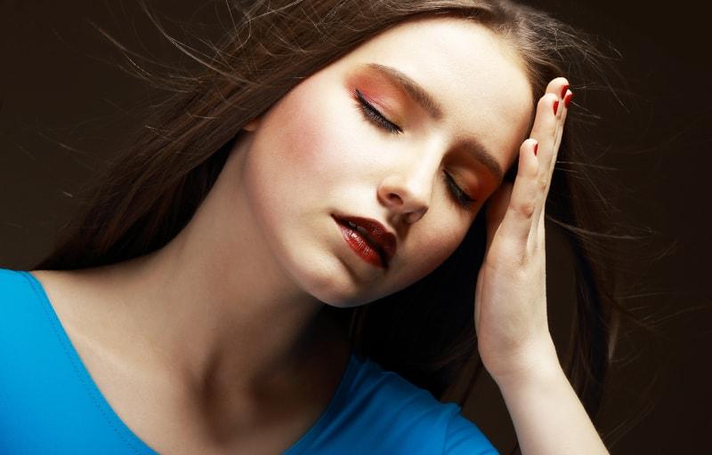 悩んで頭を痛める女性