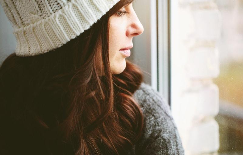 穏やかに窓から外を見る女性
