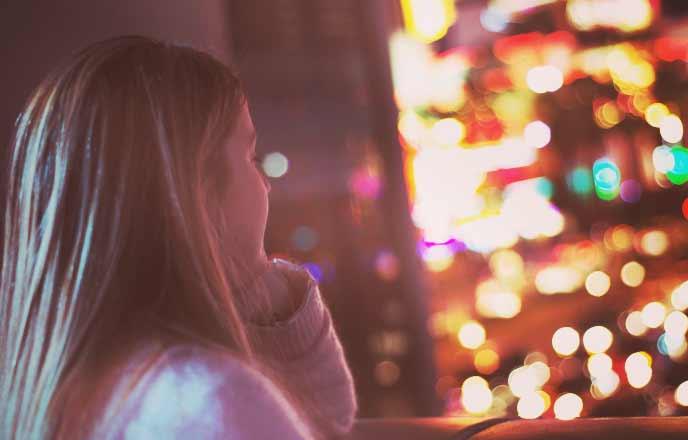 窓から夜の街の風景を眺める女性