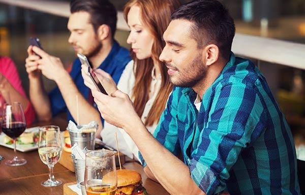 食事中にスマホを見る男女