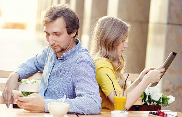 カフェでスマホを見るカップル