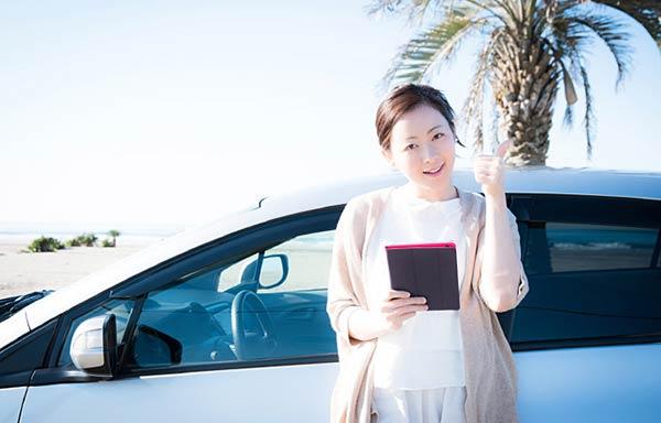 新しい車でビーチを楽しむ女性