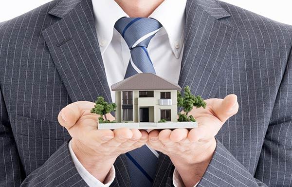 ミニチュアの家を両手に持つ不動産