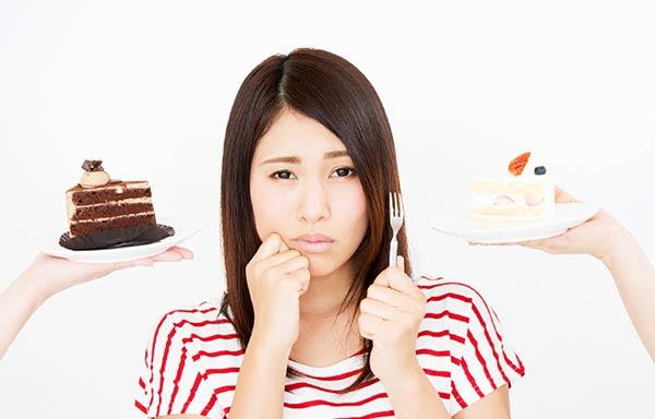 ケーキを我慢している女性