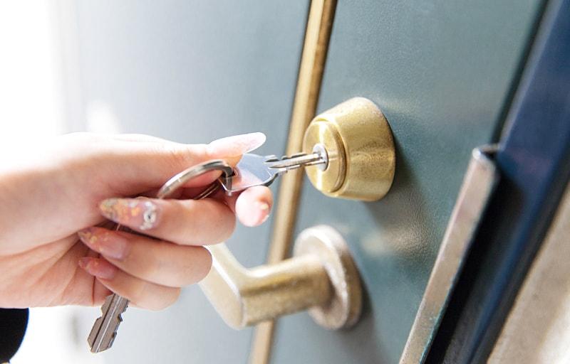ドアの鍵を閉める女性