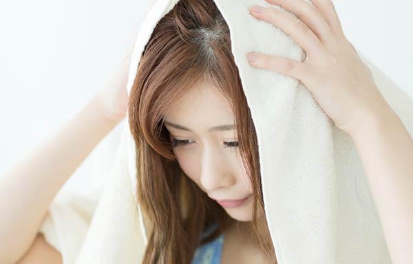 タオルで髪を乾かす女性