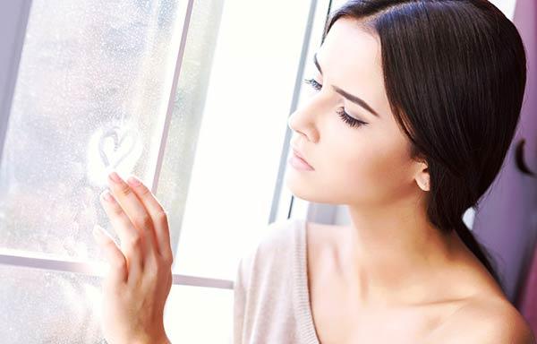 窓にハートを描く女性