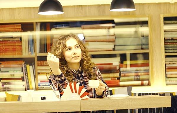 図書館でコーヒーを飲む女性