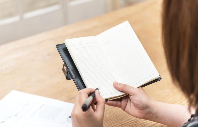 手帳にスケジュールを描く女性
