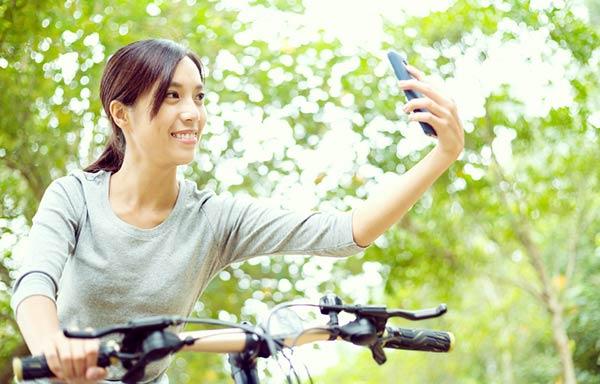 自転車にのりながらスマホで自撮りする女