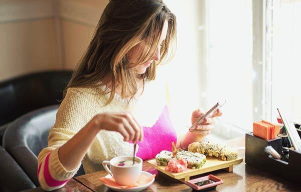 食事中にスマホを見る女性