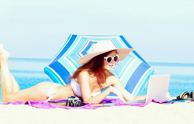 ビーチで日傘をさす女性