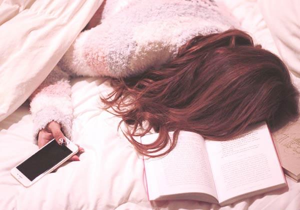スマホを片手に寝たふりをする女子