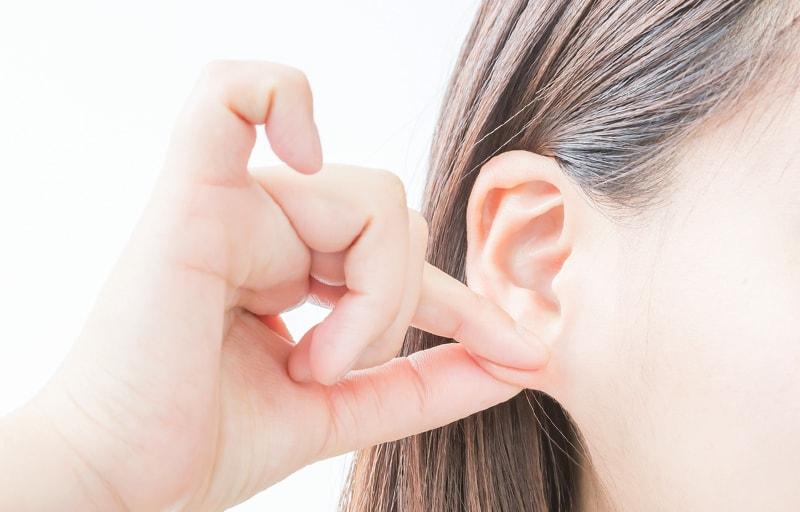 耳たぶをマッサージする女性